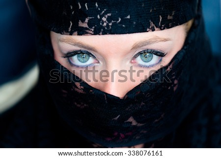 Veiled woman with blue eyes - stock photo