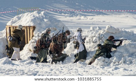 VELIKIE LUKI, RUSSIA - FERUARY 23, 2018: Soldiers behind the show trench during the  Reconstruction of a battle between Red Army and German Wehrmacht of the World War 2