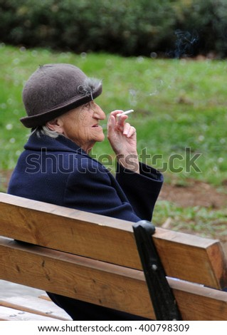 VELIKO TARNOVO, BULGARIA - MARCH 11, 2016: Aged Caucasian lady sits on the bench in the park in the early spring and smokes a cigarette - stock photo