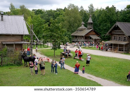 Veliky Novgorod, Russia - August 19, 2012 - Rural landscape, peasant houses, singers in traditional costumes at the Museum of Wooden Architecture Vitoslavlitsy - stock photo