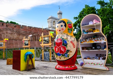 VELIKY NOVGOROD, RUSSIA -JUNE 11, 2016. Architecture view - Belfry of St Sophia cathedral with big colorful Russian doll matrioshka on the foreground and souvenirs in Veliky Novgorod, Russia