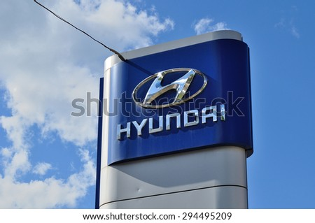 VELIKY NOVGOROD, RUSSIA - JUNE 27, 2015. Hyundai (South Korean car manufacturer headquartered in Seoul, South Korea) dealership logo against blue sky - stock photo