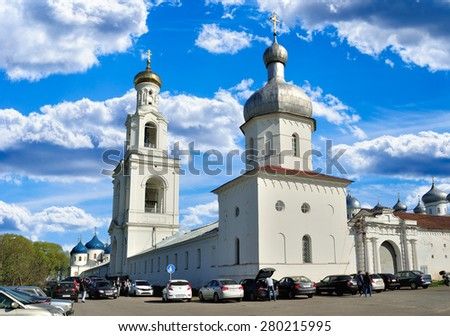 VELIKY NOVGOROD, RUSSIA - MAY 10, 2015.  The bell tower, corner tower and Church of Exaltation of the Cross in Russian orthodox Yuriev Monastery, and parishioners walking along - stock photo