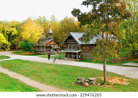 VELIKY NOVGOROD, RUSSIA - OCTOBER 4, 2015.  Autumn rural landscape, old wooden chapel and peasant hut at the Museum of Wooden Architecture Vitoslavlitsy  - stock photo