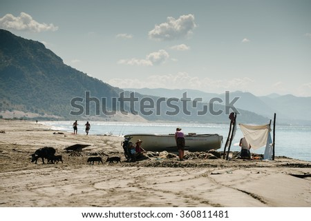 Velipoje, Albania - August 18: A few fishermen on the shores of the Adriatic Sea Fishing trawl nets near their boats in Albania and the Balkans. - stock photo