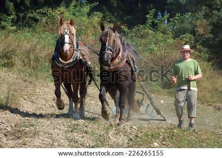 VELKA LHOTA, CZECH REPUBLIC - SEPTEMBER 26, 2009: Farmer works on his field with his horses. - stock photo