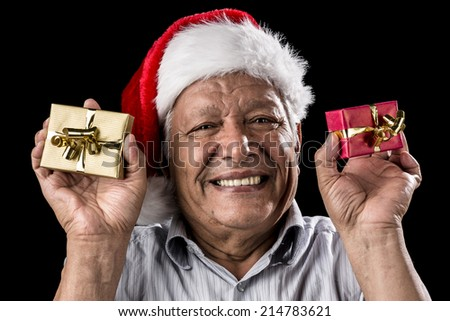 Venerable man brimming over with a smile. He is wearing a Kris Kringle hat. Holding up a small wrapped gift in each hand, golden and red. Christmas theme. Black background. Focus on eyes. Ample DOF. - stock photo