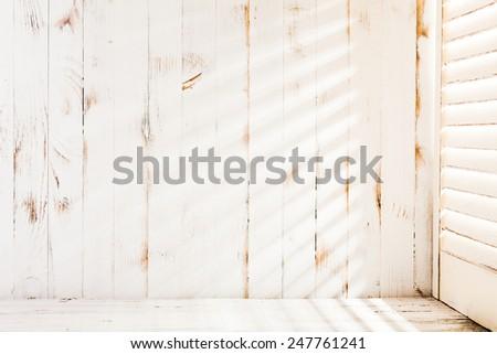Venetian blinds sunlight on the shabby wooden wall - stock photo