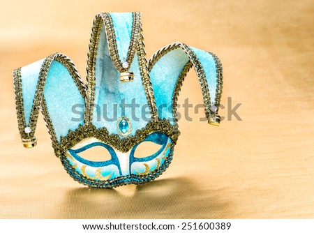 Venetian carnival mask harlequin over golden background. Festive decoration. - stock photo