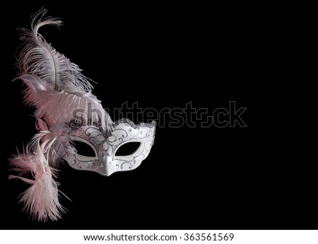 venetian carnival mask with feathers on black background with free space for text. Red tone on the left side