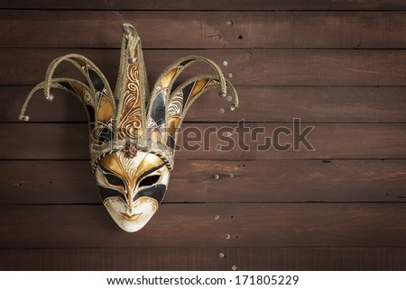 Venetian carnival mask with golden and white hues on a brown wooden background with copy space - stock photo