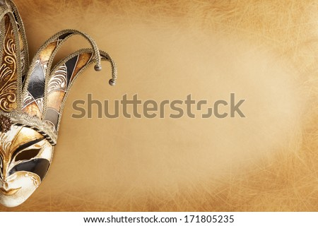 Venetian carnival mask with golden and white hues on a golden textured background with copy space - stock photo