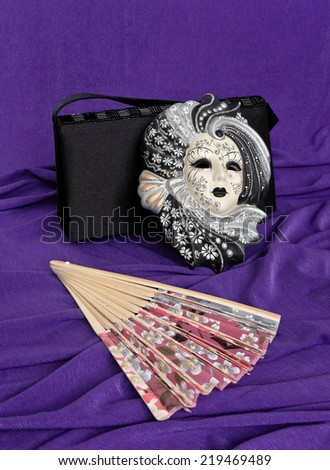 Venetian mask and fan are on the background of draped fabric - stock photo