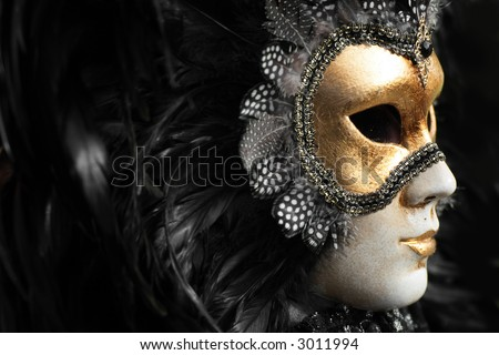 Venetian mask decorated with gold leaf and embedded with fowl feathers. - stock photo