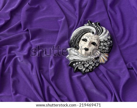 Venetian mask is on the background of draped fabric - stock photo
