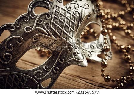 Venetian mask on wooden background - stock photo