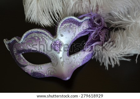 Venetian mask with feathers on a dark background