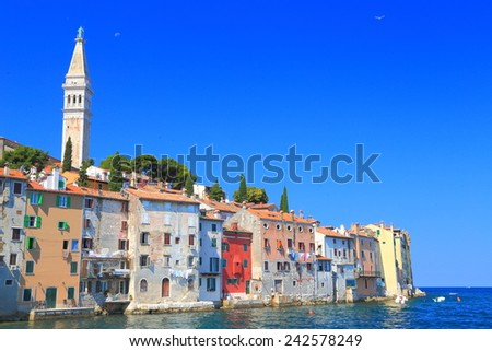 Venetian town with tall church and old buildings surrounded by the Adriatic sea, Rovinj, Croatia - stock photo