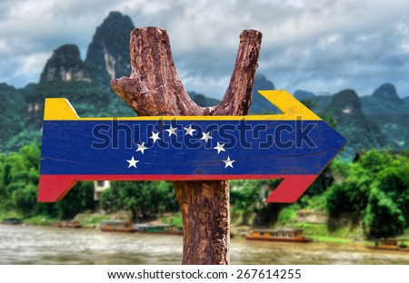 Venezuela Flag wooden sign with countryside background - stock photo