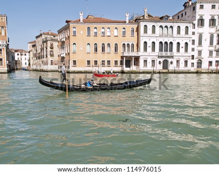 VENICE - APR 10 : Unidentified gondolier  transports tourists along the Grand Canal,  on April 10, 2011 in Venice, Italy.The gondola is a traditional Venetian transportation since ancient times.
