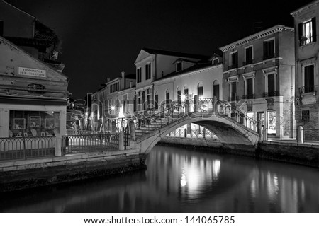 Venice at night street photo monochrome. Long exposure, supported camera. Blurred motion on curtain due to wind and on people due to long exposure. - stock photo