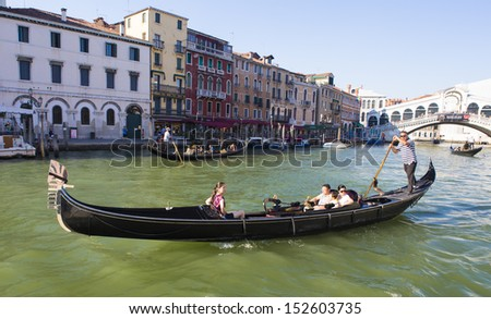 VENICE-AUGUST 18: Gondolier rides gondola on the canals in Venice on August 18, 2013. Gondola is one of the symbols of Venice and major mode of touristic transport in Venice, Italy.