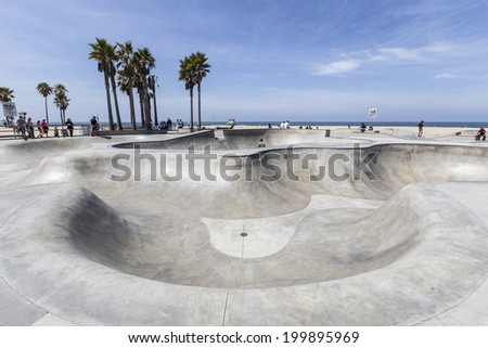 VENICE BEACH, CALIFORNIA - JUNE 21 : Deep concrete ramps and palm trees at the popular public skate board park at Venice Beach on June 21, 2014 in Los Angeles, California. - stock photo