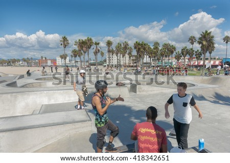 VENICE BEACH CALIFORNIA, USA OCTOBER 6;, USA Skaters discuss the action at Skate Park Venice Beach with famous palm trees and boardwalk in distance October 6, 2015, Venice Beach,California, USA