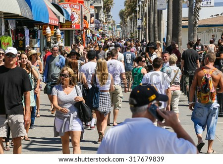 VENICE BEACH, USA - JUNE 4, 2014: The crowded Venice Beach Boardwalk. Lots of people are strolling down the boardwalk. On the sides there are several shops and palm trees. - stock photo
