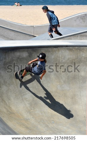 VENICE, CA - SEPTEMBER 1, 2014: Two boys ride skateboards in Venice, California on September 1, 2014. One rounds a curve as the other moves diagonally on a different part of the course.