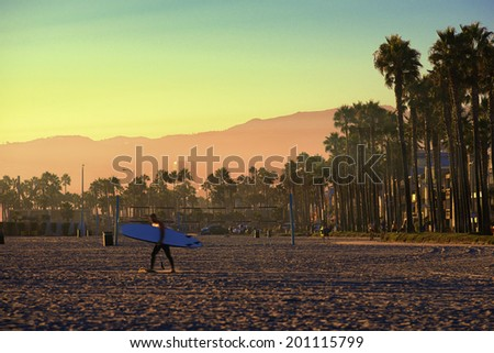 Venice, California, Surfer walking into golden sunset. - stock photo