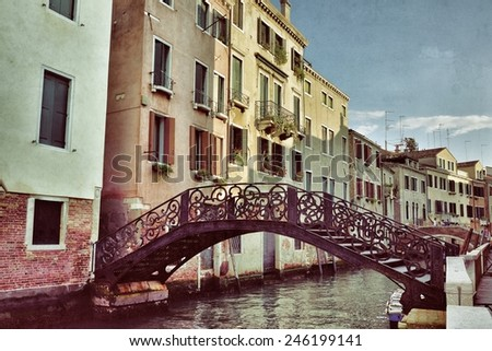 Venice canal and forged openwork bridge at sunset. Tourists from all the world enjoy the historical city of Venezia in Italy, famous UNESCO World Heritage Site.
