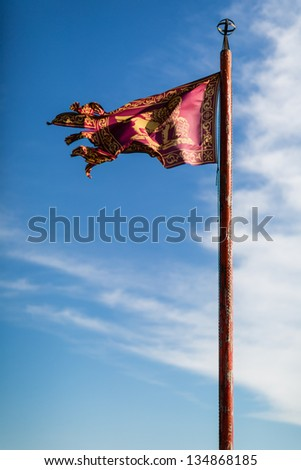 Venice flag  with blue sky in the background - stock photo
