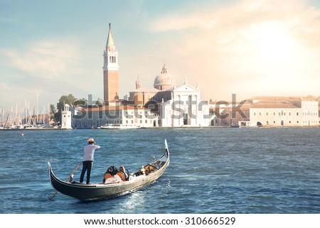 Venice gondola tour at sunset - stock photo