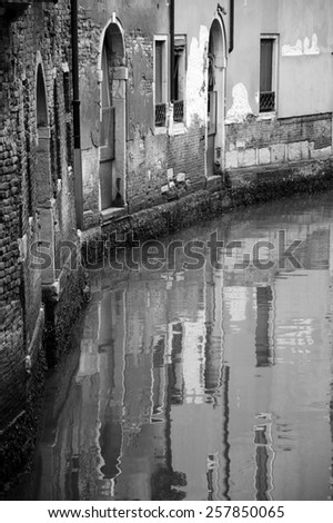 Venice houses reflection in canal. Curve. Aged photo. Black and white. - stock photo