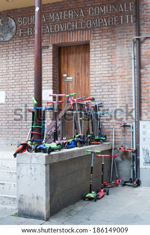 VENICE, ITALY, APRIL 2, 2014:Several junior push scooters with three wheels for children are parked in front of a nursery school on April 2, 2014 in Venice, Italy. - stock photo