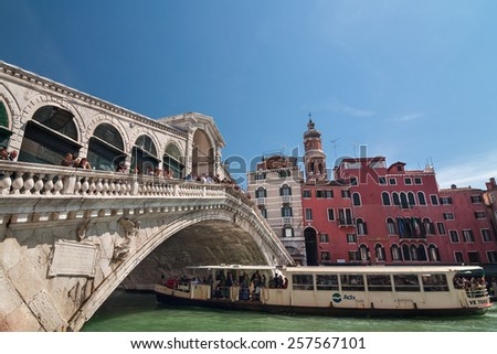 VENICE, ITALY - APRIL 13, 2013: Tourist float in boat under Rialto bridge on Grand Canal, Venice, Italy