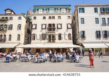 VENICE, ITALY - APRIL 22, 2016: Unidentified people in front of a restaurant in a square of the city on a sunny day - stock photo