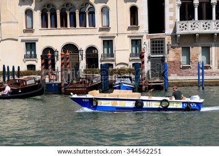Venice, Italy - August 21, 2015: Blue boat with cardboard boxes in Grand Canal in sunny day.