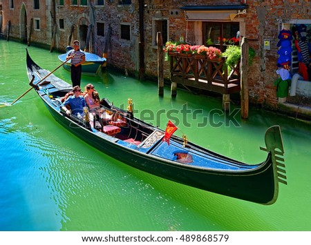 Venice, Italy - August 11, 2016: Canal with gondola in Venice. The profession of gondolier is controlled by a guild, which issues a limited number of licenses - 425