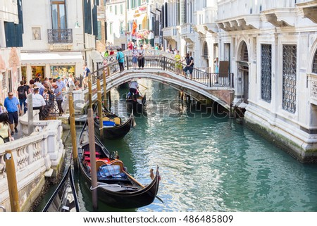 VENICE, ITALY- AUGUST 3, 2016: Tourists enjoying the gondolas in a canal. The gondolas are the most popular and romantic transportation in the city.