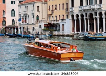 Venice, Italy - August 21, 2015: Tourists inside the luxury water taxi (a motor boat) in the Grand Canal. Bort number VE 9311