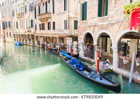 VENICE, ITALY - AUGUST 3, 2016: Tourists waiting for the gondolas in a canal. The gondolas are the most popular and romantic transportation in the city.