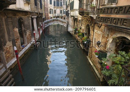 VENICE, ITALY - CIRCA APRIL, 2013: Traditional Italian trattoria restaurant overlooks small canal in the historic center of the city.