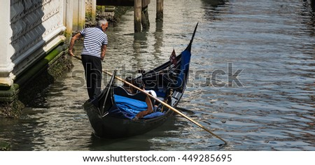 VENICE, ITALY - CIRCA MAY 2016 - Italian Gondolier sails his Gondola with people on board through the Bridge of Sighs circa May 2016 in Venice. Bridge built in the seventeenth century for prisoners - stock photo