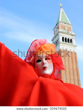 VENICE, ITALY - FEBRUARY 16, 2015:A mask at St Mark's Square and the bell tower of St Mark's Basilica at background. The Carnival in Venice is annual event which ends on Shrove Tuesday. - stock photo