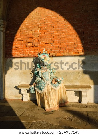 VENICE, ITALY - FEBRUARY 16, 2015: A mask in sunlight near Doge's Palace in St Mark's Square during traditional Carnival. The Carnival in Venice is annual event which ends on Shrove Tuesday. - stock photo