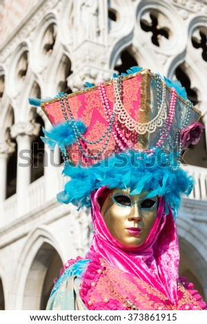 VENICE, ITALY - FEBRUARY 16, 2015: An unidentified person with a colorful carnival costume and a golden mask, posing in front of the Doge's Palace during the Carnival of Venice in Italy. - stock photo
