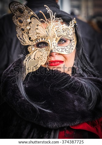VENICE, ITALY - 02 FEBRUARY 2016: Attractive woman in butterfly mask and elegant costume poses for photographers at the 2016 Venice Carnival, Italy