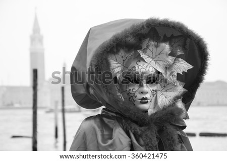 VENICE, ITALY - FEBRUARY 14, 2015: Autumn Mask in St Mark's Square square (with view on San Giorgio Maggiore island) during Carnival. The Carnival in Venice is annual event ending on Shrove Tuesday. - stock photo